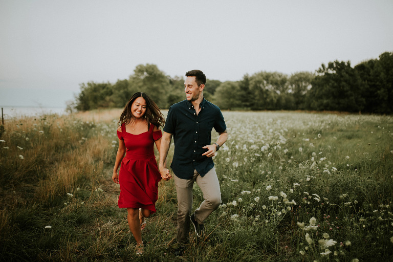 A couple runs through a field of flowers together